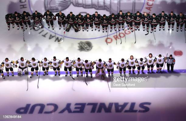 General view of the players standing on ice, with locked arms, as the United States national anthem is played before the exhibition game between the...