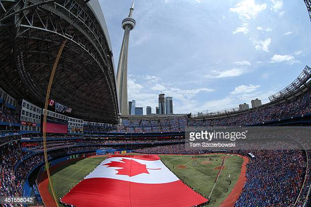 A general view of the Rogers Centre on Canada Day as a large Canadian flag is unfurled on the field during the singing of the Canadian anthem before...