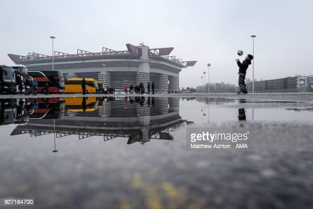 A general view of the San Siro stadium as a young boy plays footballl in the empty coach park at the postponed serie A match between AC Milan and FC...