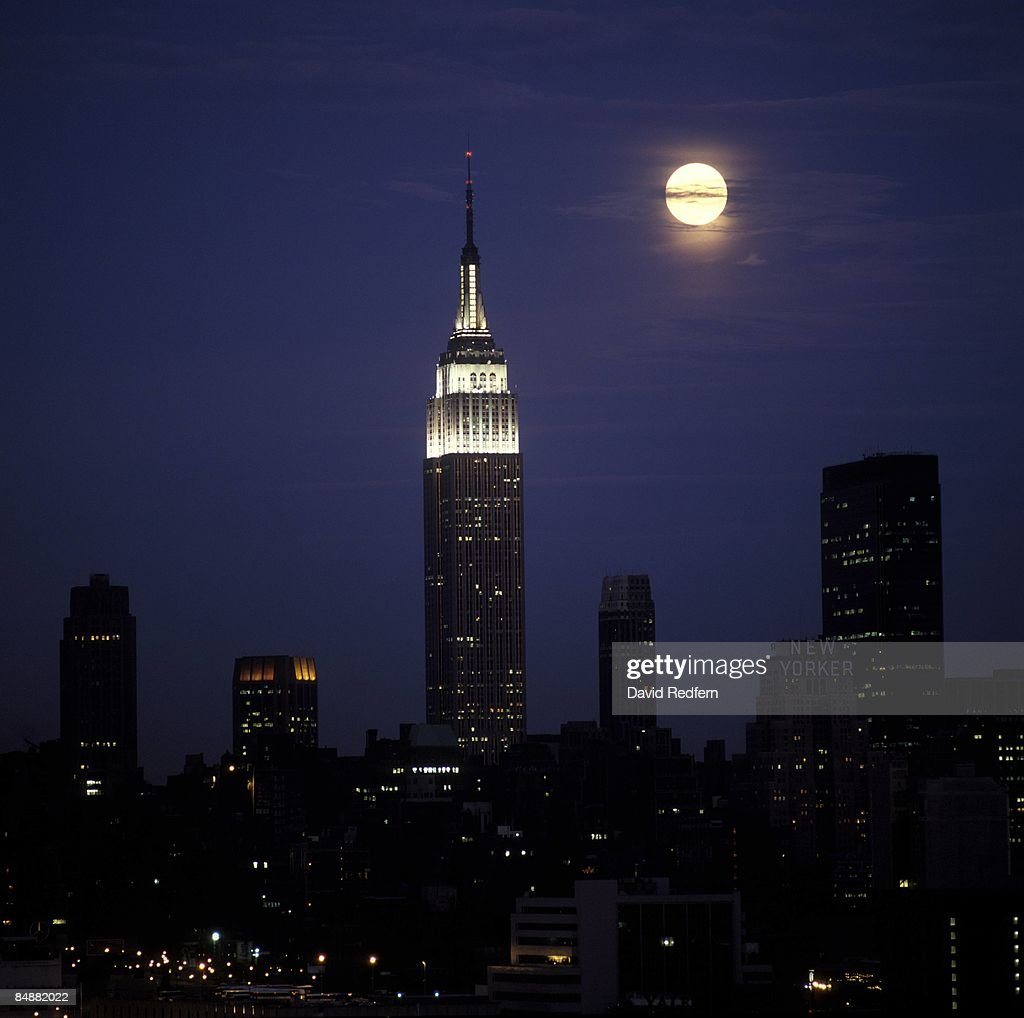 A general view of the skyline of Manhattan, New York City at night showing the moon next to an illuminated Empire State Building. Circa 1975.