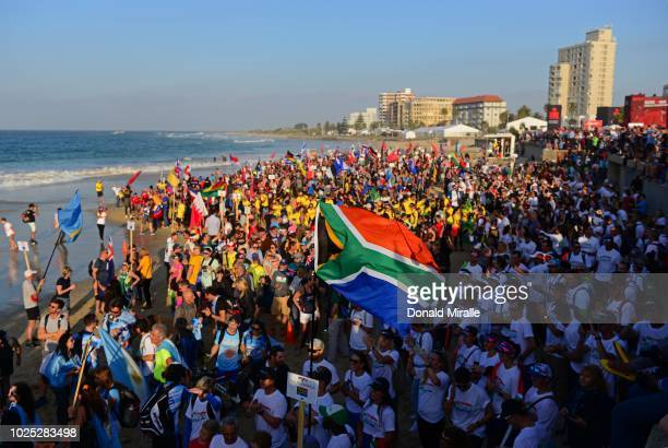 A general view of the South African flag and athletes lines up on the beach during the parade of Nations leading up to the Isuzu IRONMAN 703 World...