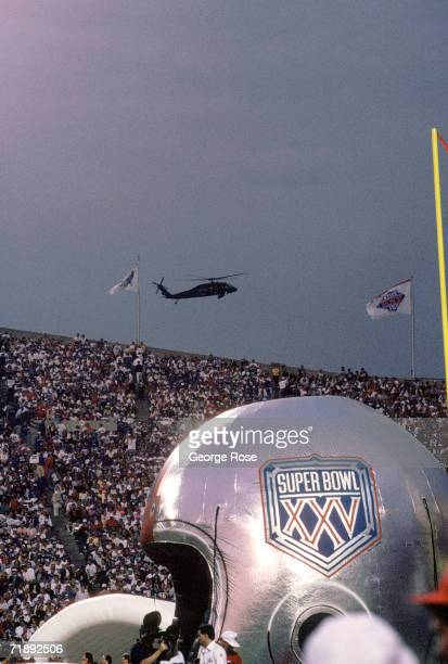 General view of the Super Bowl XXV logo on an inflatable helmet as a military helicopter patrols the air space above Tampa Stadium looking for...