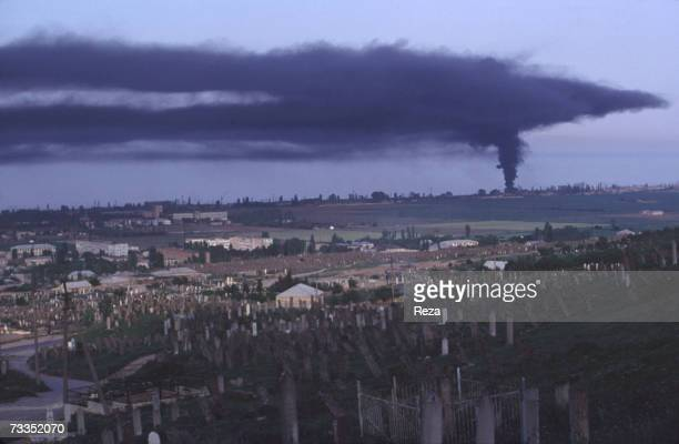 General view of the town and an historic Ottoman Empire cemetery as plumes of black smoke pours from a tire factory on September 1997 in Derbent...