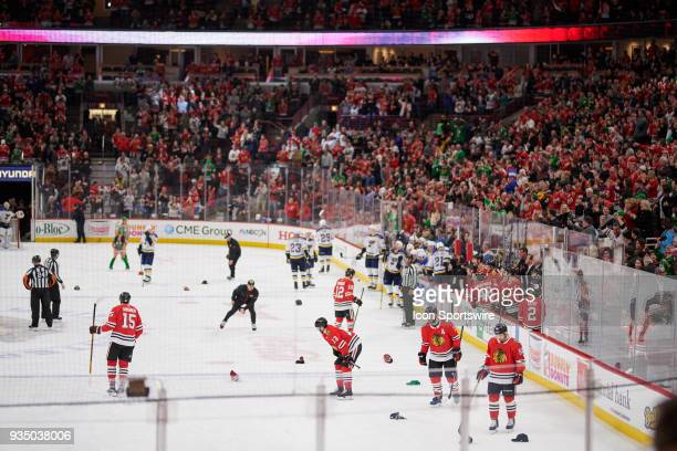 A general view of the United Center as the ice crew helps to pick hats thrown by fans after Chicago Blackhawks right wing Alex DeBrincat scored a...
