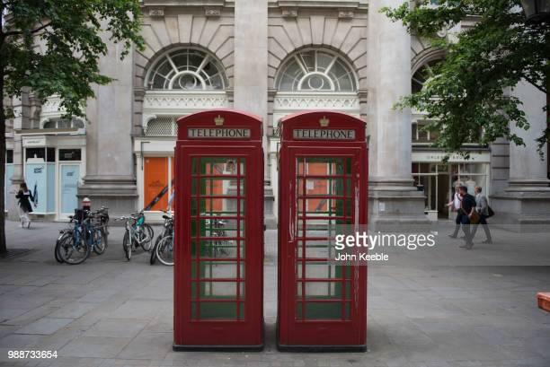 A general view of two iconic traditional red phone boxes with gold royal crown on June 19 2018 in London England