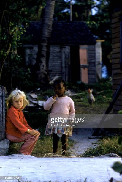 General view of two young girls sit and stand near a fence on April 28 1956 in Green Turtle Cay Abaco Bahamas