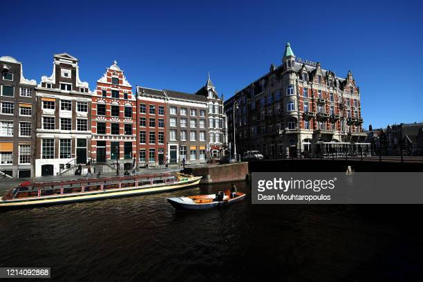 General view on the Singel Canal with people enjoying a boat ride near Koninklijk Paleis or The Royal Palace Amsterdam which will follow national...