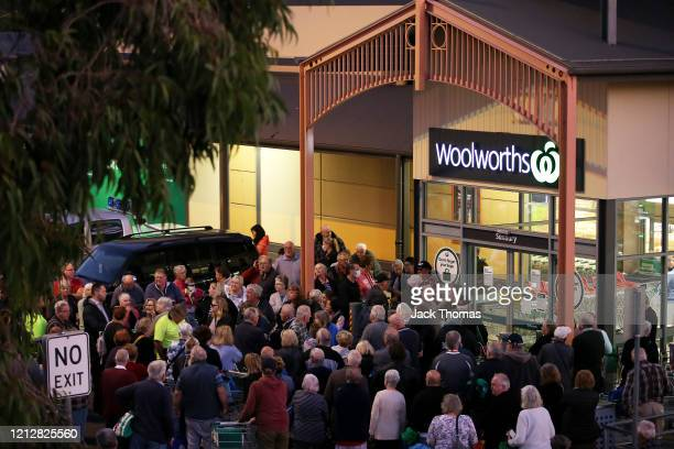 General view outside a Woolworths in Sunbury as people wait outside on March 17, 2020 in Various Cities, Australia. Australian supermarket chains...