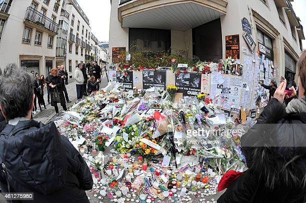 General view outside the French satirical magazine Charlie Hebdo where people arrived to pay their respects placing flowers, pens and drawings on...