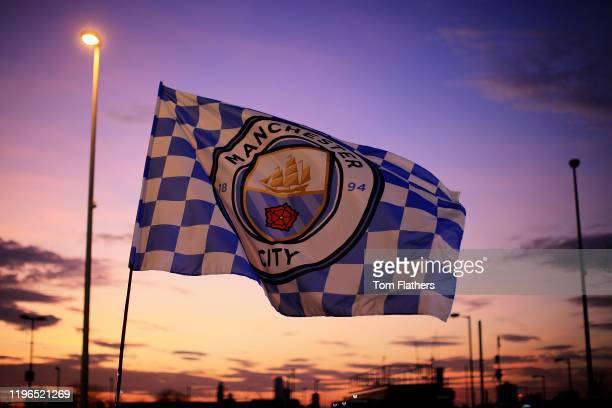 General view outside the stadium as a Manchester City flag blows in the wind as the sun sets behind ahead of the Premier League match between...