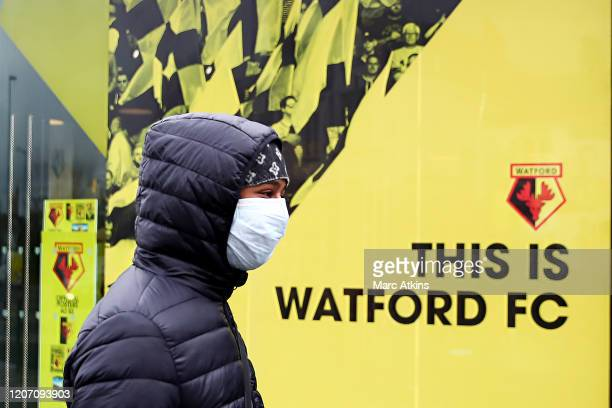 General view outside Vicarage Road, home of Watford FC as a youth walks past wearing a protective face mask on the weekend all Premier League matches...