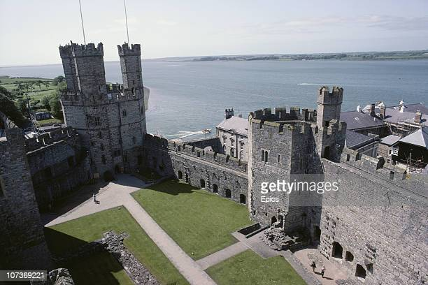 A general view overlooking the fortifications of Caernarfon Castle Gwynedd Wales June 1983 Caernarfon castle is located at the southern end of the...