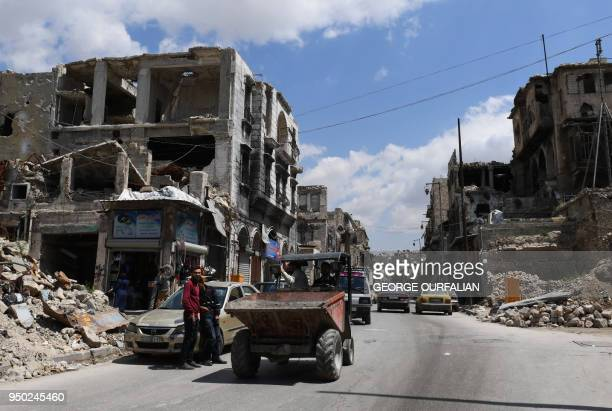 A general view show a bulldozer driving down a damaged street the Bab alNasr area in the old city of Aleppo on April 22 as Syrians start to restore...