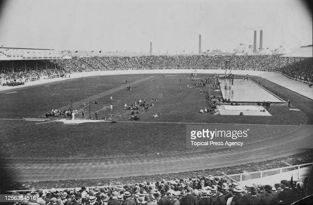 General view showing figures on the field of play beside the swimming pool at White City Stadium, built for the 1908 Summer Olympics, with crowds of...