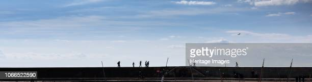 General view showing people walking on the Cobb harbour wall in silhouette. Artist James O Davies.