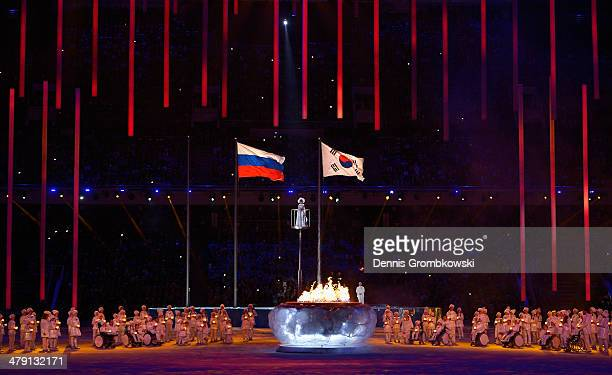 General view showing the flags of Russia and South Korea with the cauldron during the Sochi 2014 Paralympic Winter Games Closing Ceremony at Fisht...