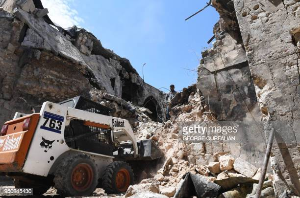 A general view shows a bulldozer shifting rubble as Syrians restore the 14th century AlSahibiyah mosque in the old city of Aleppo on April 22 2018...