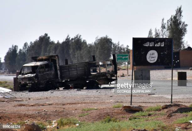 A general view shows a burnt out vehicle next to a banner bearing the Islamic State group's flag in the village of Dibsiafnan on the western...