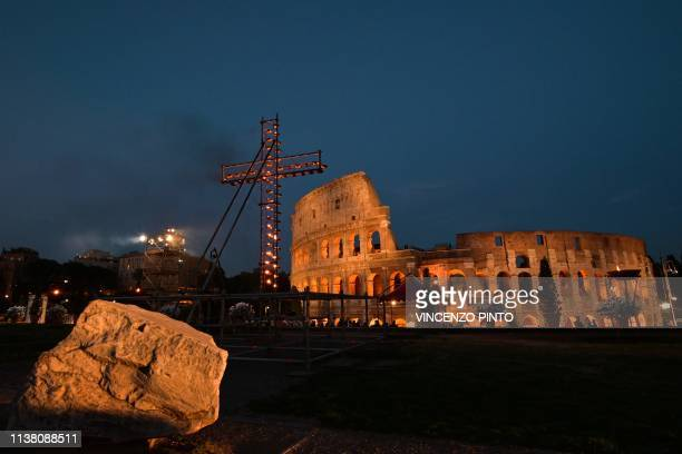 A general view shows a cross lit with candles by the Colosseum monument prior to the Pope's arrival for the Via Crucis torchlight procession of Good...