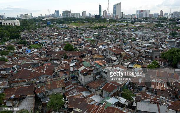 A general view shows a large slum area in front of skyscrapers in the distance in a suburb of Manila on July 5 2013 The Philippines said on July 5 it...
