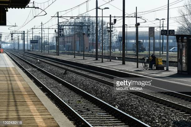 A general view shows a man working for a delivery service seated by his bicycle on a platform of the deserted railway station in Codogno southeast of...