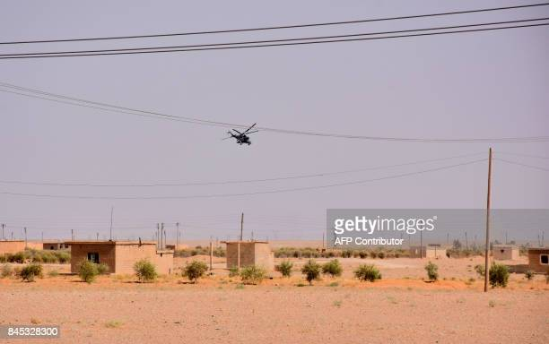 A general view shows a military helicopter flying over the outskirts of the eastern city of Deir Ezzor on September 10 as Syrian government forces...