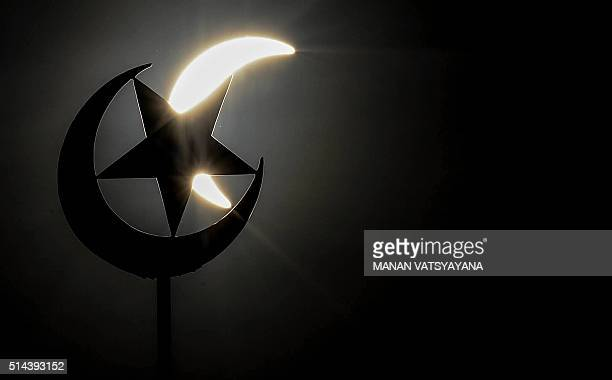 A general view shows a partial solar eclipse behind a star and crescent symbol atop a mosque in Kuala Lumpur on March 9 2016 A total solar eclipse...