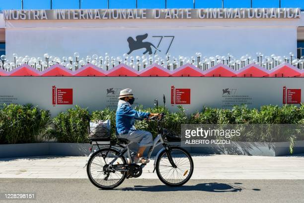 General view shows a person ride a bicycle past plants and a wooden wall built outside the festival's palace in order to prevent the public from...