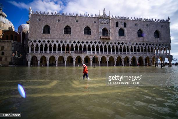A general view shows a person walking across the flooded St Mark's Square by the Doge's palace on November 14 2019 in Venice Much of Venice was left...