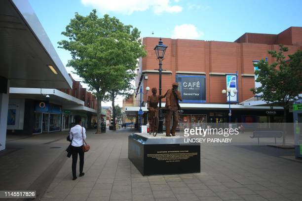 General view shows a shopper walking past the Scunthorpe Steelworkers Sculpture on the high street in Scunthorpe, north east England on May 22, 2019....