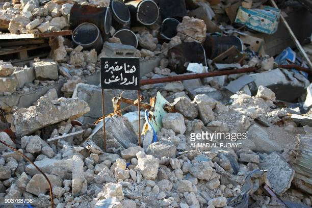 A general view shows a sign reading in Arabic 'Here is a cemetery of the Islamic State group' in the middle of the rubble in the old city of Mosul on...