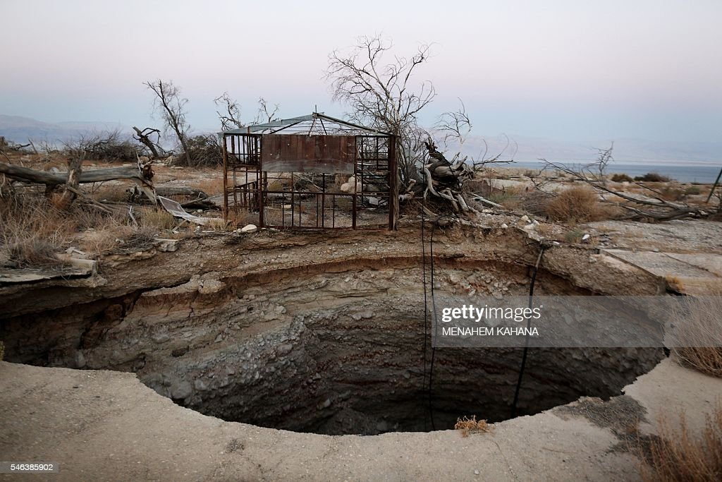 A general view shows a sinkhole in Israel's abandoned tourist resort of Ein Gedi on the shore of the Dead Sea on July 11, 2016. Experts have warned that the Dead Sea, the lowest and saltiest body of water in the world, is on course to dry out by 2050, with the emergence of sinkholes forcing the closure of roads and beaches, as well as damaging agriculture. / AFP / MENAHEM