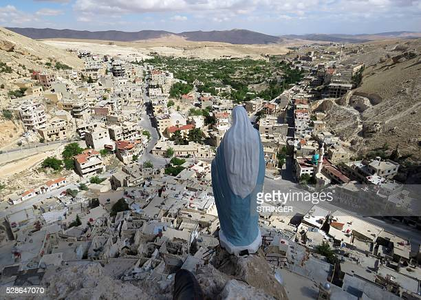 TOPSHOT A general view shows a statue of the Virgin Mary overlooking the ancient Christian town of Maalula 56 kilometers northeast of the Syrian...
