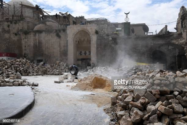 A general view shows a Syrian man cutting stones as they restore the 14th century AlSahibiyah mosque in the old city of Aleppo on April 22 2018...