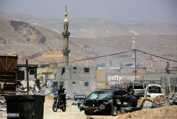 A general view shows a Syrian man on a motorbike n the former rebelheld Syrian town of Douma on the outskirts of Damascus on April 19 five days after...