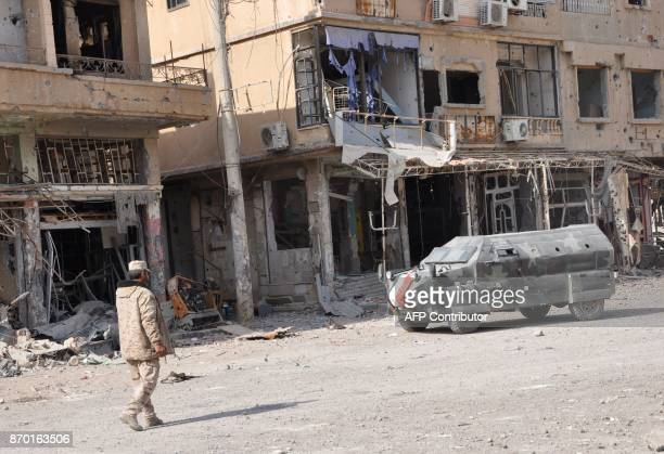 A general view shows a Syrian progovernment forces member walking past damaged buildings in the eastern city of Deir Ezzor on November 4 2017 Syrian...