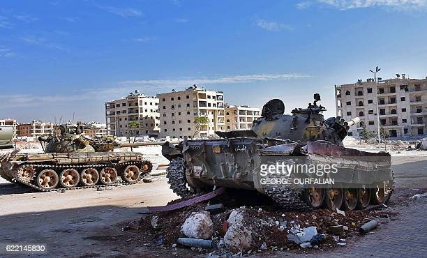 A general view shows a tank belonging to progovernment forces parked next to a destroyed tank on a mainroad in Aleppo's western Minyan district on...