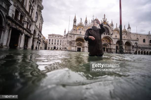 A general view shows a woman walking across the flooded St Mark's Square by St Mark's Basilica on November 15 2019 in Venice two days after the city...