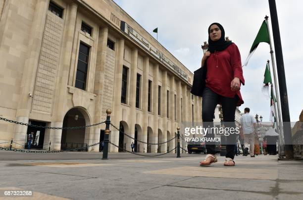 A general view shows a woman walking past the exterior of the National People's Congress in Algiers on May 23 2017 during the official nomination of...