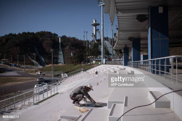 A general view shows a worker at the nordic skiing venue of the Pyeongchang 2018 Winter Olympic games near the Alpensia resort in Pyeongchang on...