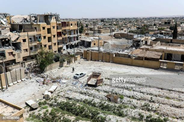 A general view shows an armed man walking through waste ground past destroyed buldings in Raqa on July 28 2017 The Syrian Democratic Forces a...
