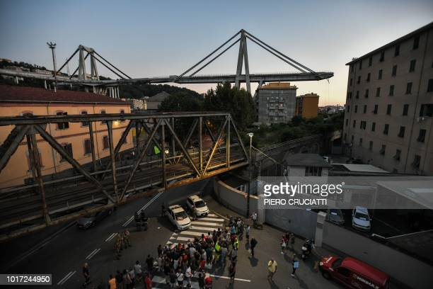 A general view shows apartment buildings under the Morandi motorway bridge in background one day after a section collapsed in Genoa on August 15 2018...