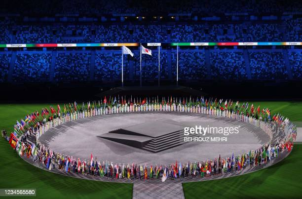 General view shows athletes carrying nations' flag stand on the field of play during the closing ceremony of the Tokyo 2020 Olympic Games, on August...