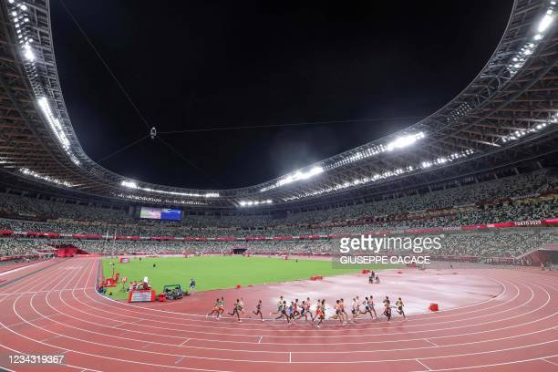 General view shows athletes competing in an empty stadium forthe men's 10000m final during the Tokyo 2020 Olympic Games at the Olympic Stadium in...