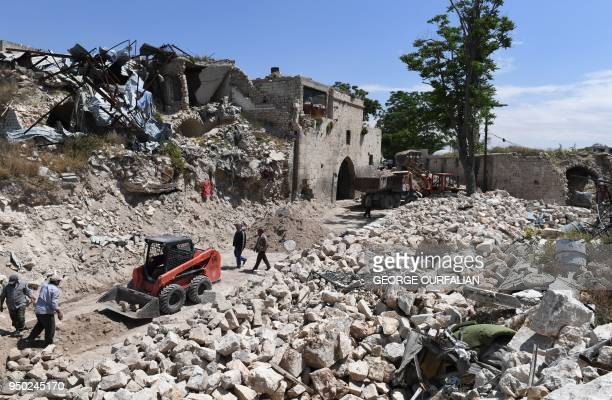 TOPSHOT A general view shows bulldozers shifting rubble as Syrians restore the alSaffahiyah area in the old city of Aleppo on April 22 2018 Following...