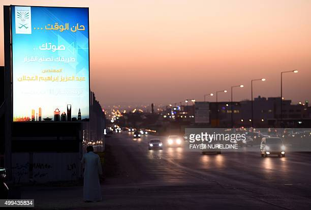A general view shows cars driving past a candidate's campaign billboard for the municipal council elections in the alSahafa district of the Saudi...