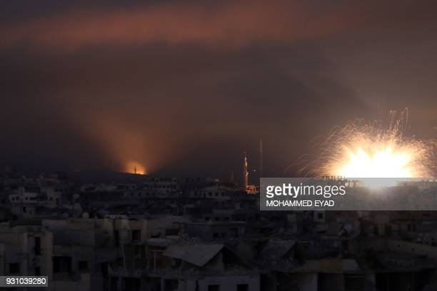 TOPSHOT A general view shows explosions lighting the sky following regime air strikes on Zamalka in the rebel enclave of Eastern Ghouta on the...