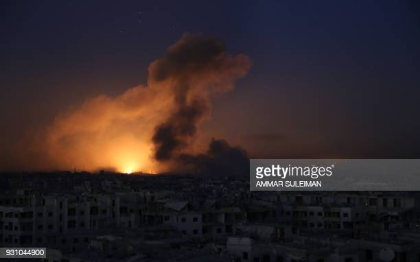TOPSHOT A general view shows explosions lighting the sky following reported regime air strikes on Zamalka in the rebel enclave of Eastern Ghouta on...