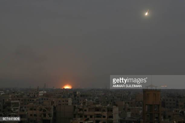 A general view shows flames rising from buildings following reported Syrian government bombardments on the rebelheld town of Saqba in the besieged...