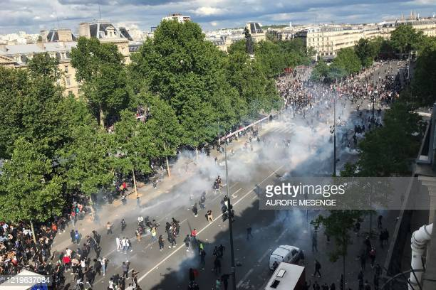 General view shows French riot police forces firing tear gas during a rally as part of the 'Black Lives Matter' worldwide protests against racism and...